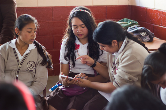 girls looking at smartphone in a workshop