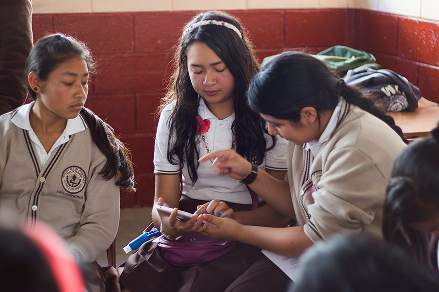 Girls learning about the use of smartphones for education at workshop in Santa Catarina Pinula