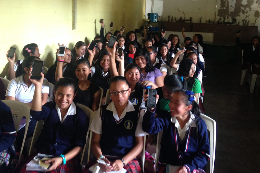 Girls holding smartphones at workshop in Accion Humana