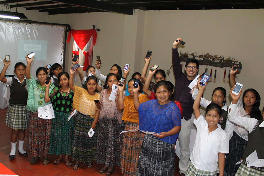 Girls holding smartphones in workshop at Plan Internacional in Alta Verapaz