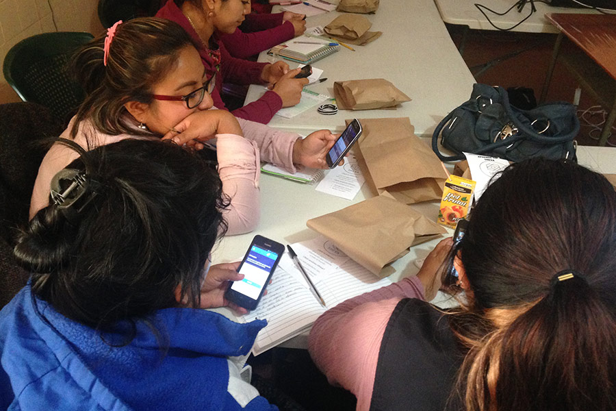 women with phones in workshop at Renacimiento Patzun